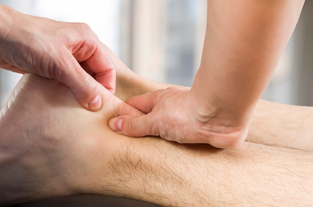Hands of chiropractor, physiotherapist doing calf muscle massage to man patient. osteopath