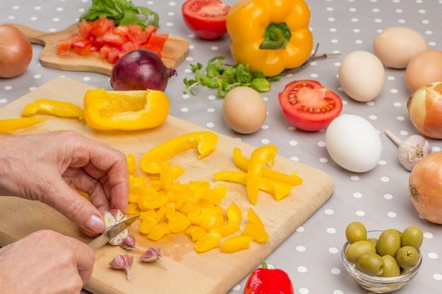 Hands chop garlic  on cutting board.