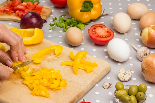 Hands chop yellow pepper on  cutting board. eggs, olives, garlic tomatoes on table