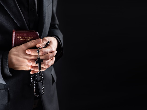 Hands of a christian priest dressed in black holding a crucifix and new testament book. religious person with bible and prayer beads, low-key image with copy space.