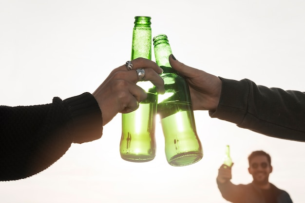 Hands clanging beer bottles on light background