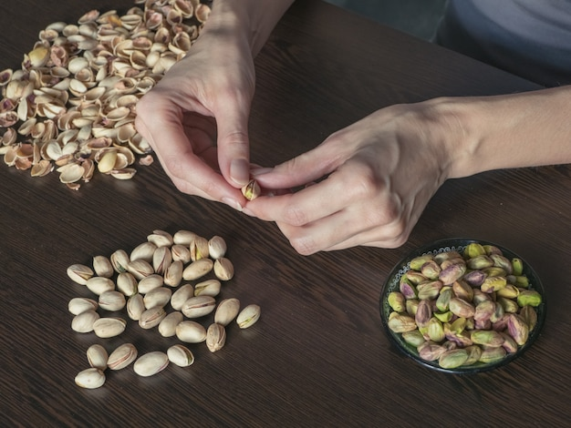 Hands clean pistachios nuts.the manual labor concept.