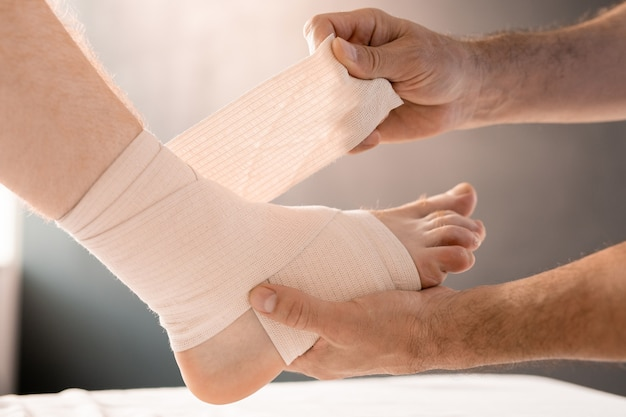 Hands of clinician wrapping foot and leg of patient with flexible bandage while holding sole of the man during medical procedure in clinics