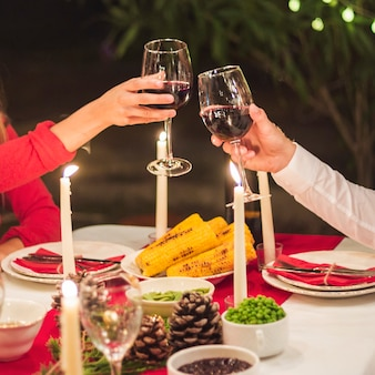 Hands clinking wineglasses at christmas dinner