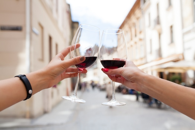 Hands close up of couple toasting glasses of wine
