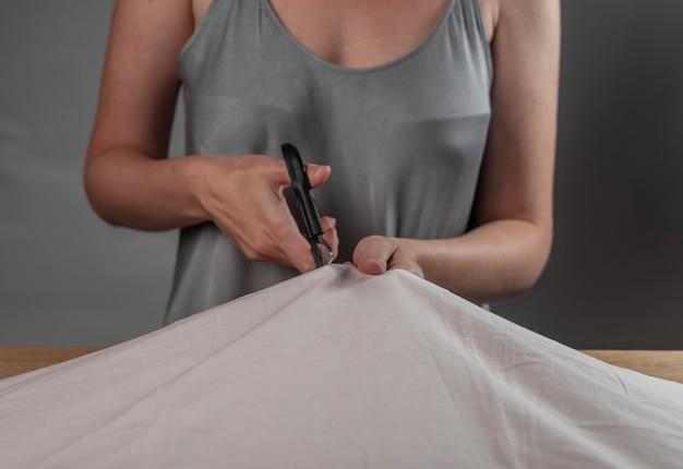 Руки заделывают резку ткани швейными ножницами