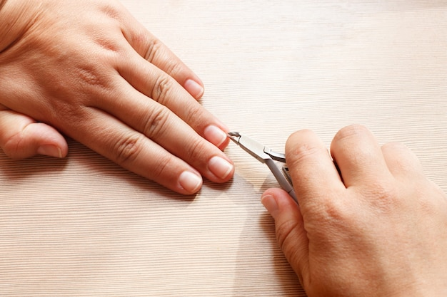 Hands close-up, a girl doing a manicure to herself, nail clippers.