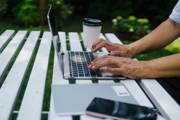 Руки заделывают старика, использующего ноутбук