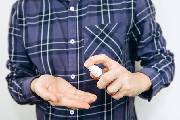 手のクローズアップ、男は彼の手に消毒剤を置きます。若い男が手に消毒液を持ち、コロナウイルスから身を守っています。 covid-2019。