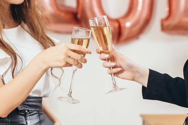 Hands close up. two women clink glasses during holiday