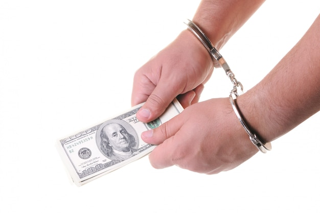 Hands in closed metal handcuffs holding money