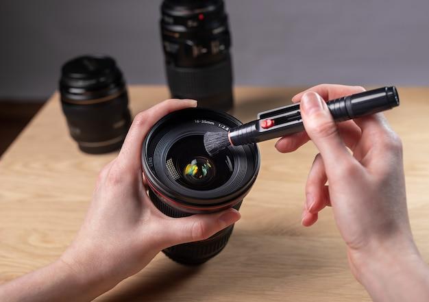 먼지를 제거하는 전문 브러시 도구로 디지털 카메라 렌즈를 청소 손 근접 촬영.
