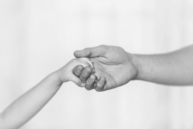 남자 아버지의 손 클로즈업은 밝은 배경에 아이의 손을 잡고 있다