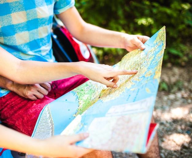 車のトランクに座りながら地図を見て若い旅行者の手のクローズアップ