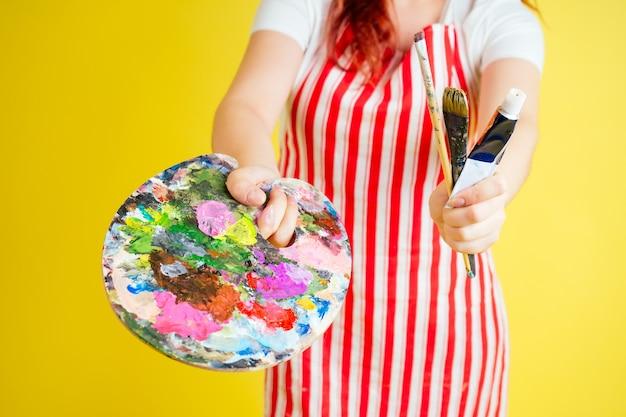 エプロンパレット、ペイントのチューブ、スタジオのピンクの背景にブラシでアーティストの画家の手のクローズアップ。ミューズとインスピレーションのアイデア。
