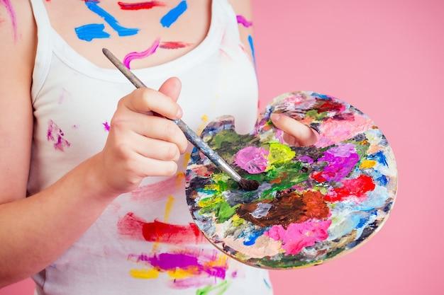 汚れたアーティストの画家の手のクローズアップは、パレット、ペイントのチューブ、スタジオのピンクの背景のブラシの隣の床に横たわっている顔のペイントからしみを汚します。ミューズとインスピレーションのアイデア。