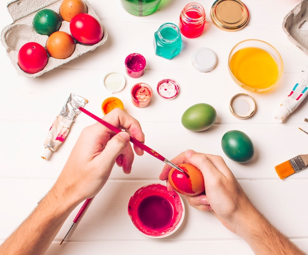 Hands coloring easter egg near container, brushes and pink dye liquid in cans