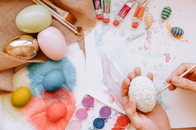 Hands coloring easter egg with brush