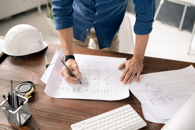Hands of contemporary architect with pencil or crayon drawing sketch of building construction while standing by table