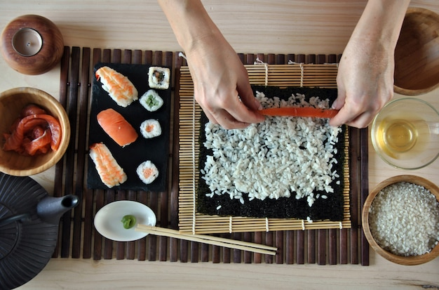 Руки готовят суши с рисом, лососем и нори
