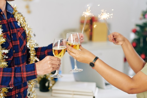 Hands of coworkers burning bengal lights and toasting with champagne glasses when celebrating new year in office