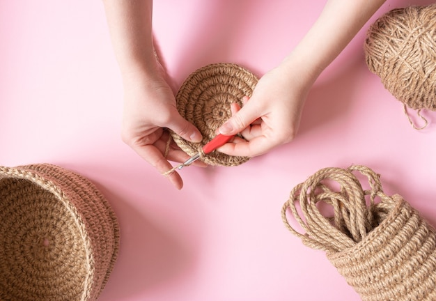 Hands crochet a round napkin made of jute