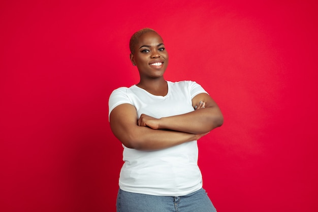 Hands crossed. african-american young woman's portrait on red. beautiful female model in shirt.