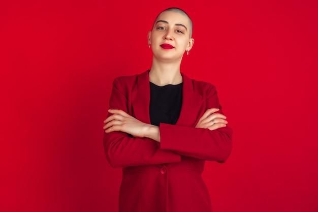 손을 건넜다. 빨간 벽에 고립 된 젊은 백인 대머리 여자의 초상화. 재킷에 아름 다운 여성 모델입니다. 인간의 감정, 표정, 판매, 광고 개념. 이상한 문화.