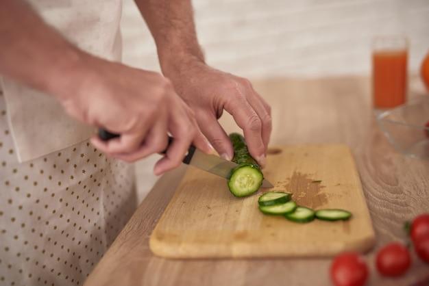 Руки нарезать огурец на тарелку приготовления овощей.