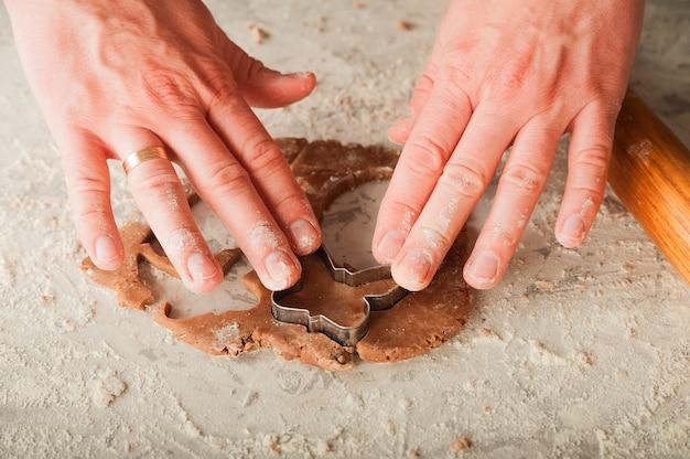 Руки вырезать пряники крупным планом. пасхальное пряничное тесто, мука, скалка и копирка.