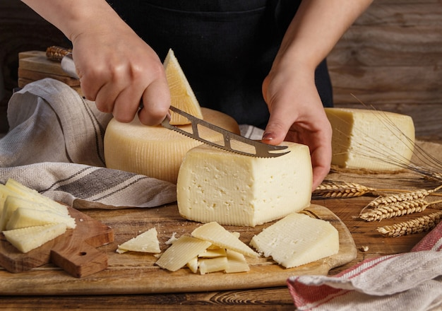 Hands cut pieces of  fresh homemade cheese on a wooden board close up