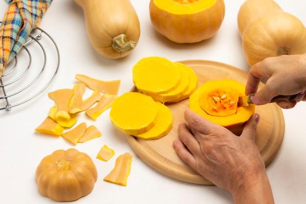 手はナイフでカボチャの種で果肉を切ります。テーブルの上のカボチャ。金属製のスタンドにナプキン。白色の背景。フラットレイ