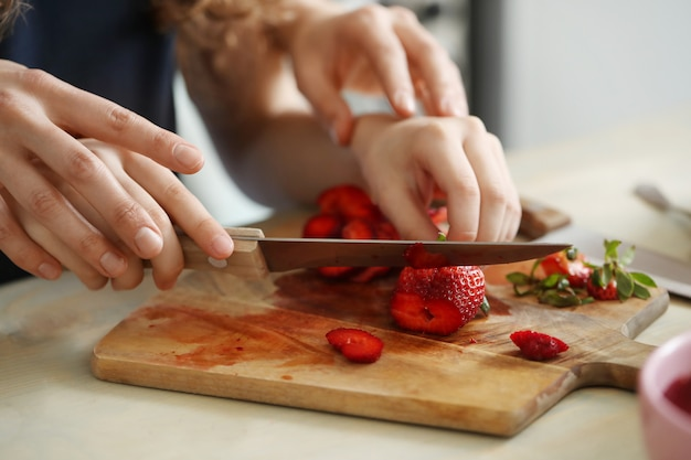 Hands cutting fresh strawberries