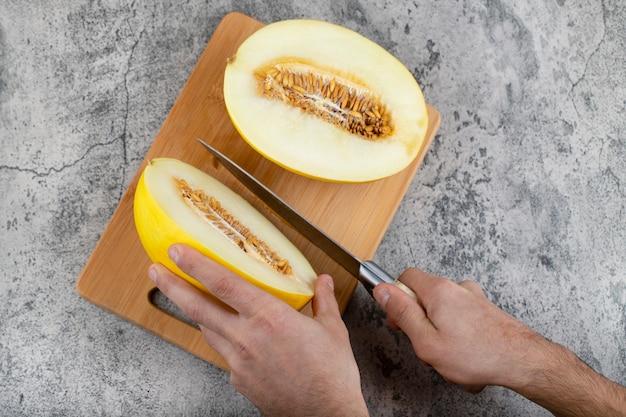 Mani che tagliano il melone giallo fresco sul tagliere di legno.