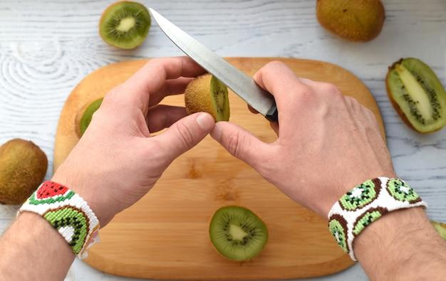 Hands cutting kiwi over cutting board