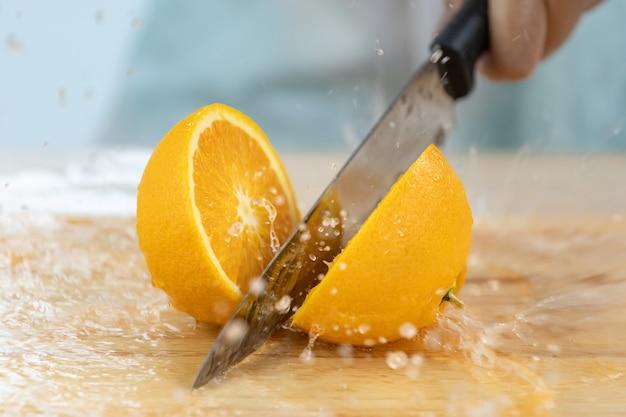 Руки резки апельсин с всплеском апельсинового сока на деревянной разделочной доске.