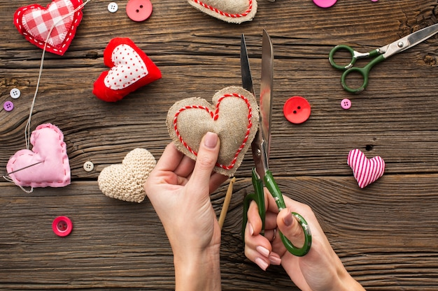 Hands cutting a red heart shape on wooden background