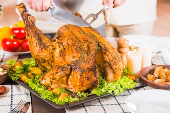 Hands cutting roasted chicken on tray
