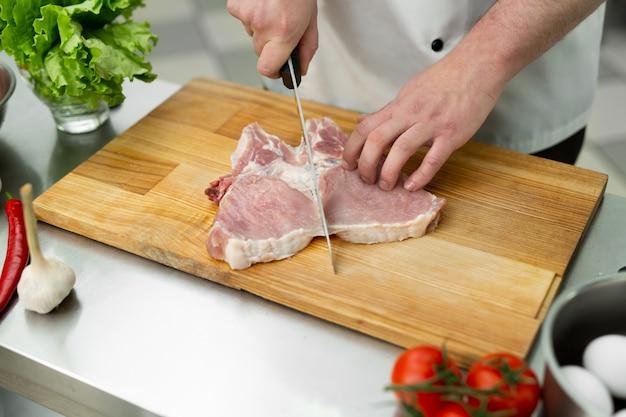Руки режут мясо на доске