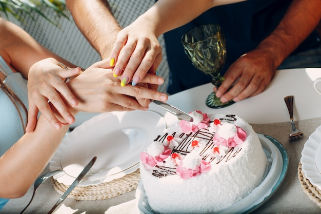 Hands cutting white cake together. happy birthday concept.