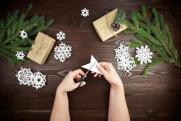 Руки, режущие снежинки из белой бумаги на деревянном столе