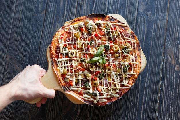 手がピザを届ける