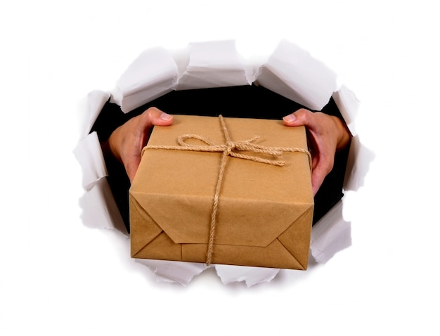 Hands delivering mail package through torn white paper background