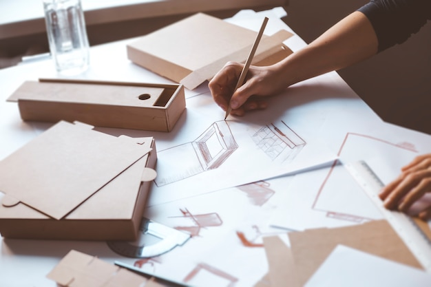 Hands designer draws a sketch of paper packaging. creative development of ecological boxes.