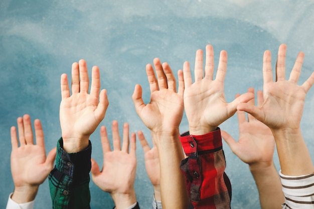 Hands of different people raised up on blue surface
