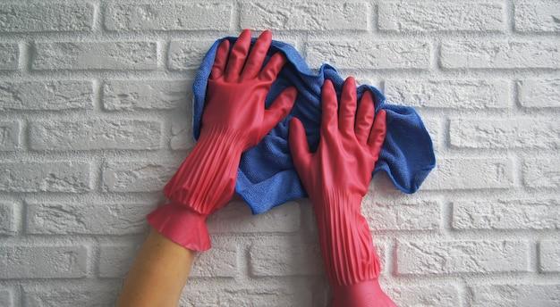 ピンクのゴムで白い壊れた壁のハンドルを手で消毒または洗浄します。クリーニングサービス。covid-19中のコロナウイルス感染の予防