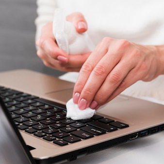 Hands disinfecting laptop keyboard