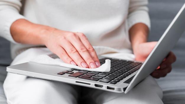 Руки дезинфицируют поверхность ноутбука