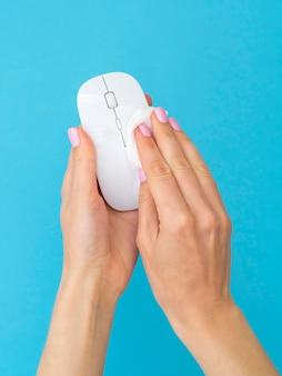 Руки дезинфицируют мышь с салфеткой