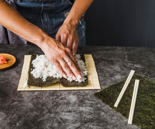 Hands dividing rice evenly on nori